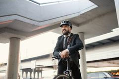 Hipster businessman commuter with electric bicycle traveling home from work in city. Copy space stock photography
