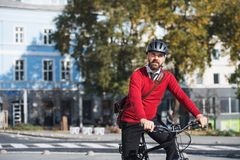 Hipster businessman commuter with electric bicycle traveling to work in city. Copy space royalty free stock photo