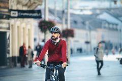 Hipster businessman commuter with electric bicycle traveling to work in city. Copy space stock photography