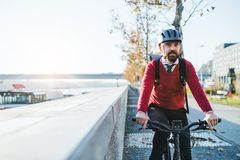 Hipster businessman commuter with electric bicycle traveling to work in city. A front view of hipster businessman commuter with electric bicycle traveling to royalty free stock images