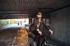 Hipster businessman commuter with electric bicycle traveling to work in city. A front view of hipster businessman commuter with electric bicycle traveling to stock photography