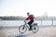 Hipster businessman commuter with electric bicycle traveling to work in city. A side view of hipster businessman commuter with electric bicycle traveling to royalty free stock images