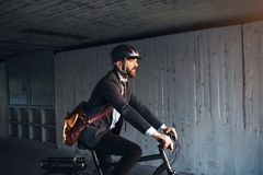 Hipster businessman commuter with electric bicycle traveling to work in city. A side view of hipster businessman commuter with electric bicycle traveling to royalty free stock photo