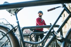 Hipster businessman commuter parking electric bicycle in city when going to work. A hipster businessman commuter parking electric bicycle in city when going to royalty free stock image