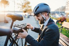 Hipster businessman commuter setting up electric bicycle in city. Hipster businessman commuter setting up electric bicycle when traveling home from work in city royalty free stock photography