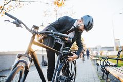 Hipster businessman commuter setting up electric bicycle in city. Hipster businessman commuter setting up electric bicycle when traveling home from work in city royalty free stock photos