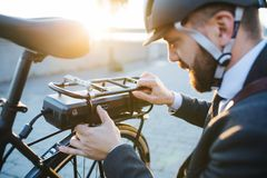 Hipster businessman commuter setting up electric bicycle in city. Hipster businessman commuter setting up electric bicycle when traveling home from work in city stock photos