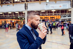 Hipster businessman drinking coffee at the train station Royalty Free Stock Image