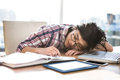 Hipster businessman falling asleep on desk Royalty Free Stock Photos