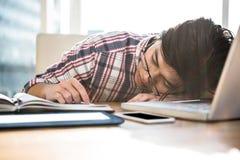 Hipster businessman falling asleep on desk Stock Photos