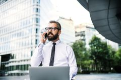 Hipster businessman with laptop and smartphone in the city. Hipster businessman with laptop and smartphone in the city, making a phone call stock photos