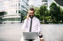 Hipster businessman with laptop and smartphone sitting outdoors in the city. stock images