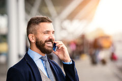 Hipster businessman making phone call waiting at the airport Stock Images