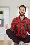 Hipster businessman meditating at his desk Royalty Free Stock Photo