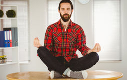 Hipster businessman meditating at his desk Stock Photo
