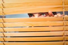 Hipster businessman peeking through blinds Royalty Free Stock Photography