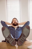 Hipster businessman relaxing at his desk Royalty Free Stock Photography