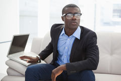 Hipster businessman sitting on couch with laptop Royalty Free Stock Images