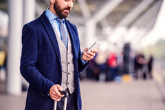 Hipster businessman with smart phone waiting at the airport Royalty Free Stock Image