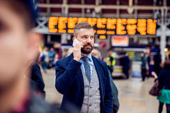 Hipster businessman with smartphone standing at the crowded stat. Hipster businessman holding a smartphone, making a phone call,  standing at the crowded station Stock Images
