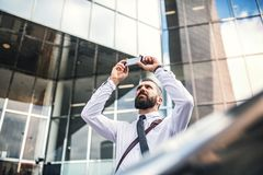 Hipster businessman with smartphone standing on the street in London, taking selfie. royalty free stock photos