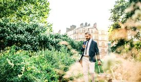 Hipster businessman with smartphone and suitcase walking in park in London. stock images