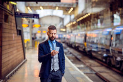 Hipster businessman with smartphone, waiting at the train platfo Stock Photos