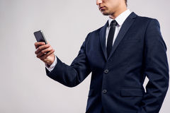 Hipster businessman with smartphone writing text message. Studio Royalty Free Stock Photo