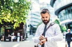 Hipster businessman standing in London city, checking the time. royalty free stock photos