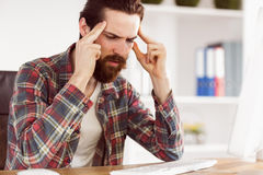 Hipster businessman stressed at his desk Royalty Free Stock Photo
