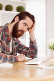 Hipster businessman stressed at his desk Royalty Free Stock Images
