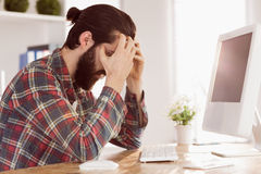Hipster businessman stressed at his desk Stock Image