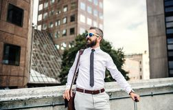 Hipster businessman with sunglasses and laptop bag standing on the street in London. royalty free stock images