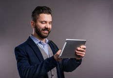 Hipster businessman with tablet, studio shot, gray background. Hipster businessman in dard blue jacket with tablet, studio shot on gray background Royalty Free Stock Photo