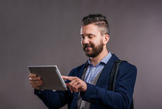 Hipster businessman with tablet, studio shot, gray background. Hipster businessman in dard blue jacket with tablet, studio shot on gray background Royalty Free Stock Images