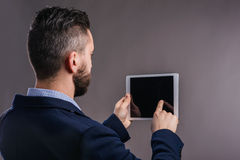 Hipster businessman with tablet, studio shot, gray background. Hipster businessman in dard blue jacket with tablet, studio shot on gray background, rear view Stock Photos