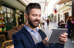 Hipster businessman with tablet. Summer day in the city. Hipster businessman in dard blue jacket with tablet. Sunny summer day in the city Stock Image