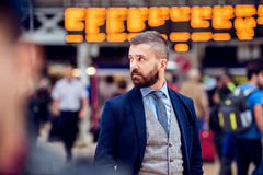 Hipster businessman waiting at the crowded London train station Stock Image
