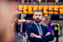 Hipster businessman waiting at the crowded London train station Stock Images