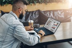Hipster businessman writing notes in notepad and working on laptop with graphs, charts, diagrams on monitor. Hipster businessman sitting indoors, writing notes stock photography