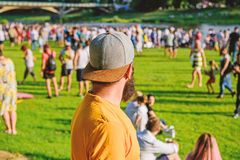 Hipster in cap happy celebrate event fest or festival. Summer fest. Man bearded hipster in front of crowd. Open air stock photos