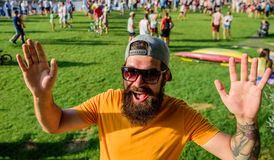 Hipster in cap happy to meet friend at event picnic fest or festival. Man bearded hipster in front of crowd people. Waving hand green riverside background stock image