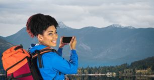 Hipster carrying backpack taking picture through smart phone standing on road against mountains stock image