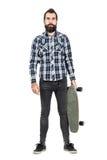 Hipster carrying skateboard looking at camera. Royalty Free Stock Image