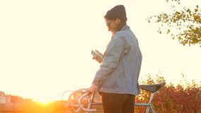 Young hipster caucasian girl with retro bicycle using mobile phone with amazing city sunset. 4k, slowmotion. Hipster caucasian girl with retro bicycle using stock video footage