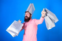 Hipster on cheerful face with bag on head is addicted shopaholic. Man with beard and mustache carries shopping bags. Blue background. Shopping concept. Guy stock photo