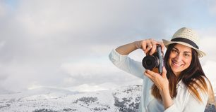 Hipster clicking photographs by snowcapped mountains against sky. Digital composite of Hipster clicking photographs by snowcapped mountains against sky Stock Photo