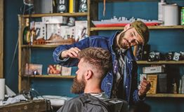 Hipster client with fresh haircut or hairstyle. Barber styling hair of bearded client with wax by hands. Barbershop royalty free stock photos