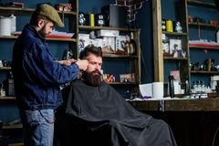 Hipster client getting haircut. Barber with hair clipper work on hairstyle for hipster, barbershop background. Barber. With clipper trimming hair on temple of royalty free stock photos