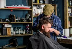 Hipster client getting haircut. Barber with hair clipper works on haircut of bearded guy barbershop background. Hipster. Hairstyle concept. Barber with clipper royalty free stock images